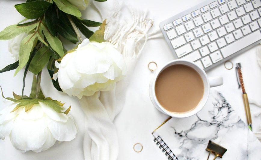 Tastatur eines PC plus weiße Pfingstrosen und Kaffeetasse auf einem Schreibtisch