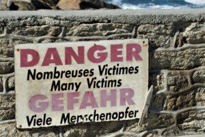Schild an einer Mauer auf Französisch und Deutsch: Gefahr! Viele Menschenopfer! Hinter der Mauer der Atlantik