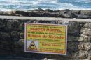 Schild auf einer Mauer vor dem Meer mit folgendem Text: Achtung, sogar klein, sind die Wellen eine sterbliche Gefahr