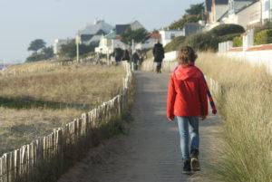 Mit Holzlatten ausgelegter Weg zwischen Dünen, rechts auch Einfamilienhäuser