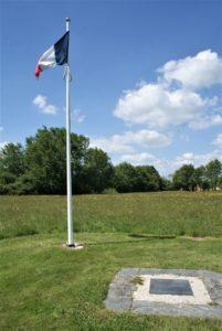 Gedenkplatte Bouvron auf Wiese mit Fahnenmast und französischer Flagge