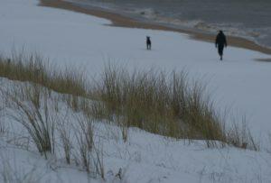 Schneebedeckte Düne, Meer und Mann mit Hund