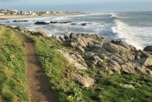 Schmaler Wanderweg große Wellen bretonische Häuser