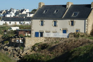 Weißes bretonisches Haus mit blauen Fensterläden vor Felsen
