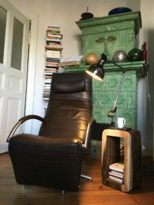 Der Relaxsessel von Caroline Elias vor einem grünen Kachelofen und Büchern