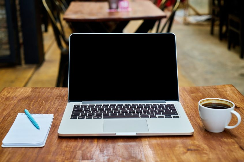 Schreibtisch mit Laptop, Notizblock und Tasse Kaffee